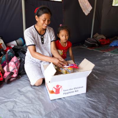 Una mamma con bambina aprono il kit igienico sanitario ricevuto da Save the Children