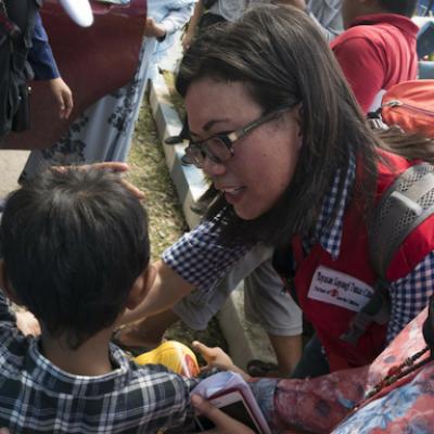 Un operatrice di Save the Children assiste un bambino in Indonesia