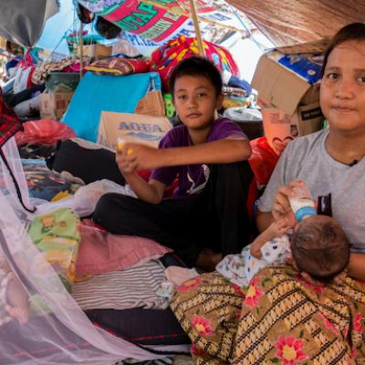 Una famiglia con bambino piccolo al riparo in un rifugio temporaneo allestito da Save the Children