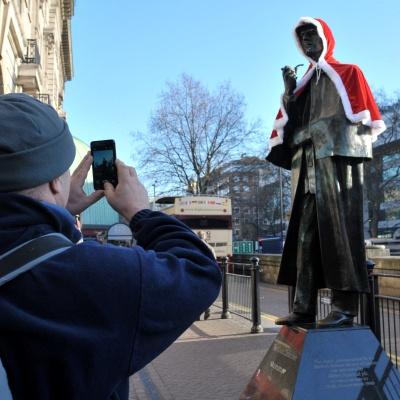 un uomo che fotografa una statua con mantello di babbo natale