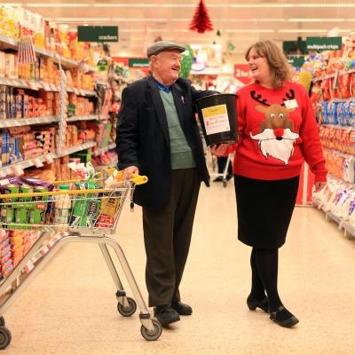 un uomo e una donna che indossa un maglione con renna in un supermercato