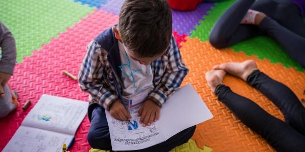 bambino seduto a gambe incrociate su un tappeto colorato intento a leggere