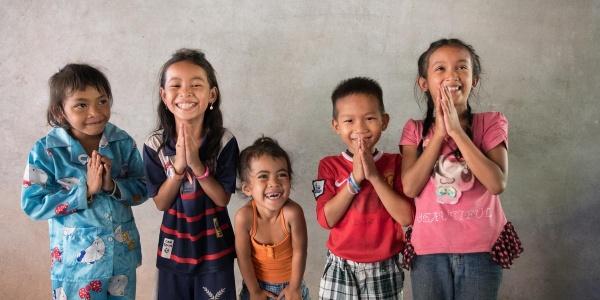 5 bambine cambogiane in piedi con le mani giunte sorridono