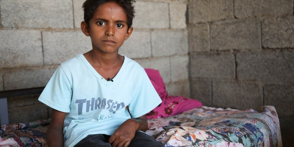 Mezzo busto bambino yemenita seduto sul letto