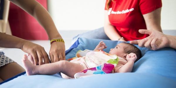 3 operatrici save the children Italia al fianco di un neonato sdraiato su un cuscino blu