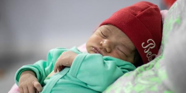 neonato con tutina verde acqua, berrettino rosso, che dorme in braccio alla sua mamma