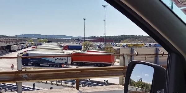 piazzale di camion ripreso dal finestrino di una macchina della quale si vede anche uno specchietto.