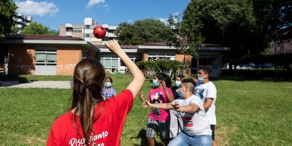 Un operatrice Save the children di spalle gioca a palla con bambini su un prato