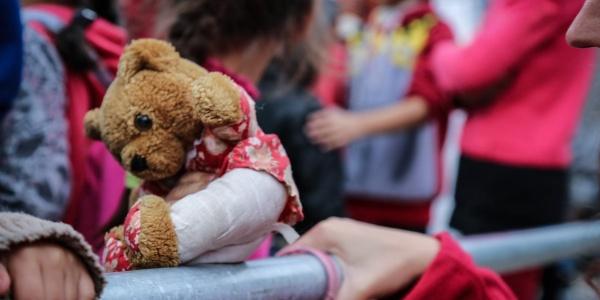 le mani di due bambini afferrano lastra di acciaio accanto a peluche in primo piano