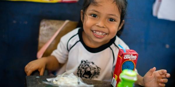 bambina filippina sorridente seduta a un tavolino a scuola mentre fa merenda