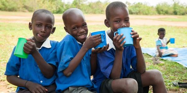 tre bambini ugandesi vestiti di blu, seduti su un ramo bevono acqua da alcune tazze colorate