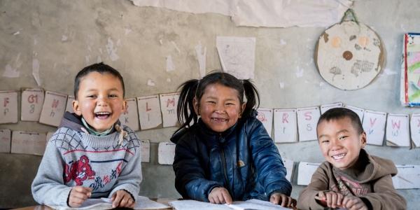 3 bambini asiatici sorridenti seduti a un banco di scuola