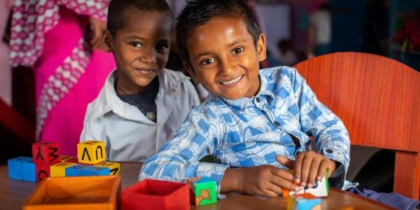 due bambini nepalesi giocano insieme seduti a un tavolo