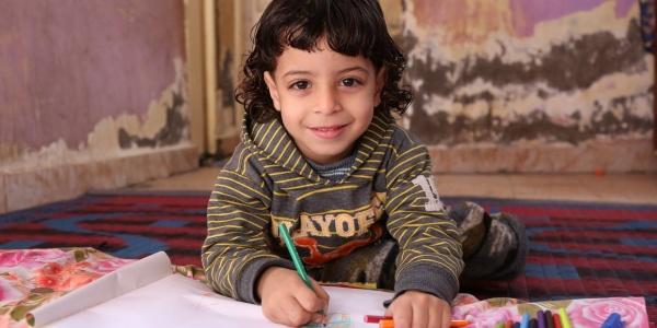 bimba egiziana con capelli neri a caschetto alla scrivania mentre disegna su un foglio bianco e guarda sorridente in camera