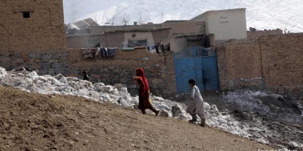 Due bambini afghani camminano in salita all interno del loro villaggio