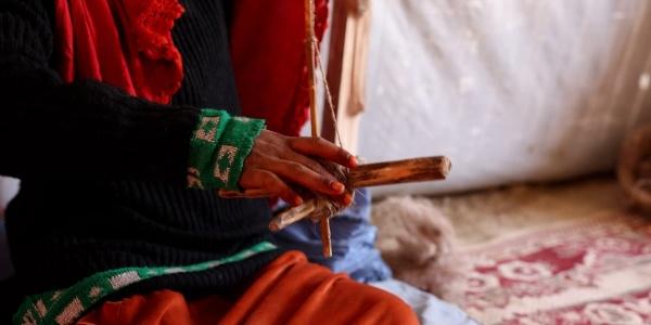 primo piano mani di una bambina che ha in mano un telaio
