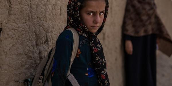 bimba afghana guarda verso di noi poggiata a un muro con uno zaino sulle spalle