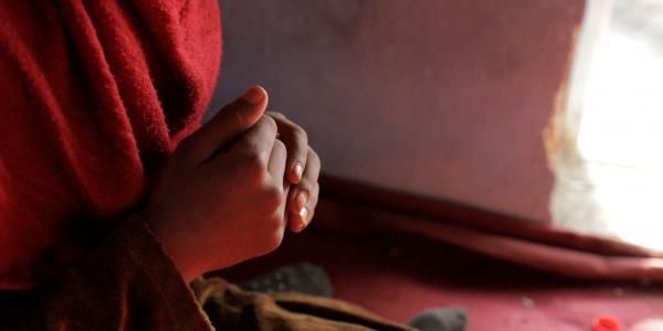 mani giunte di una bambina anonima che indossa un vestito rosso.