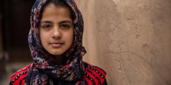 Mezzo busto di bambina afghana con chador blu a fiori rossi