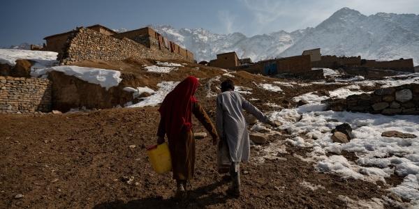 Due bambini di spalle portano una tanica ognuno con un braccio mentre cammninano.