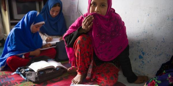Bambine afghane sedute a terra studiano con quaderni davanti a loro