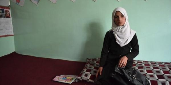 Bambina afghana con chador bianco seduta sul letto guarda in camera