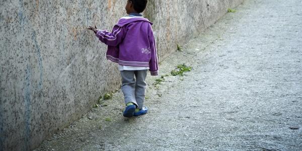Bambino migrante cammina di spalle toccando muro grigio