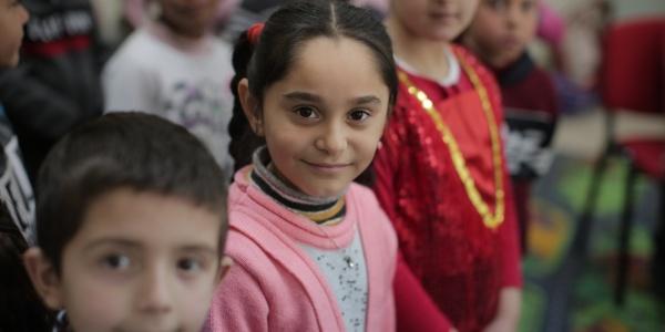 4 bambini albanesi guardano in camera e sono vestiti in modo tradizionale e molto colorato