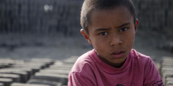 Primo piano di bambino nepalese costretto a lavorare in fabbrica di mattoni