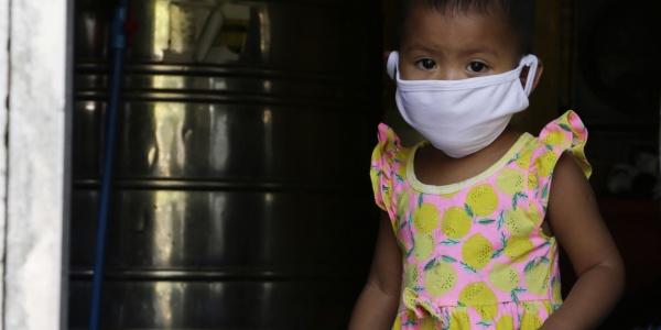Bambina asiatica con mascherina bianca sul volto.