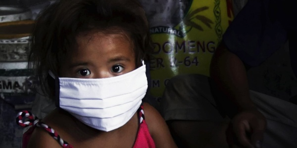 Primo piano bambina asiatica con mascherina bianca in volto