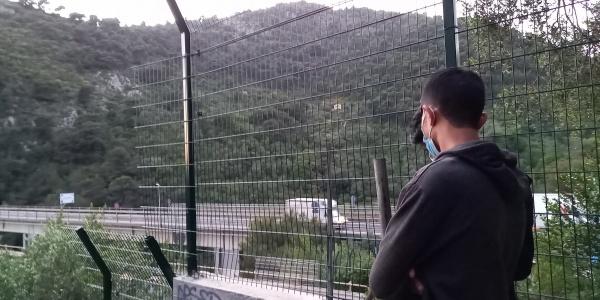 Ragazzo preso di spalle indossa una felpa grigia e guarda davanti a sé. Si trova all aperto e di fronte a sé ha una rete e oltre una collina alberata.