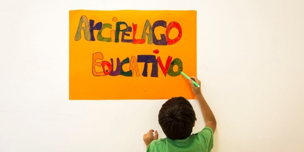 Bambino di spalle con maglietta vede scrive su un cartello appeso al muro le parole arcipelago educativo
