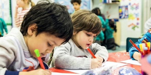due bambini di 5 anni disegnano con matite seduti a tavolino