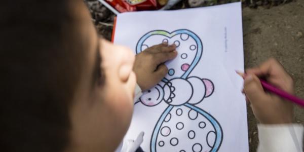 bimbo in primo piano a sinistra sfocato mentre disegna una farfalla colorata su un foglio davanti a sè