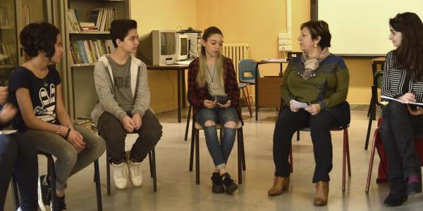 3 ragazzi e 2 insegnanti seduti sulle sedie disposte in cerchio in aula per fare il circle time