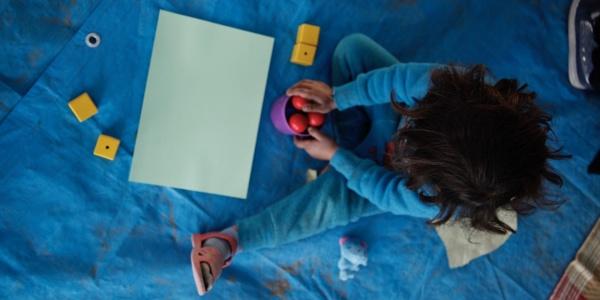 foto dall alto di bimba seduta per terra mentre gioca con delle palline rosse