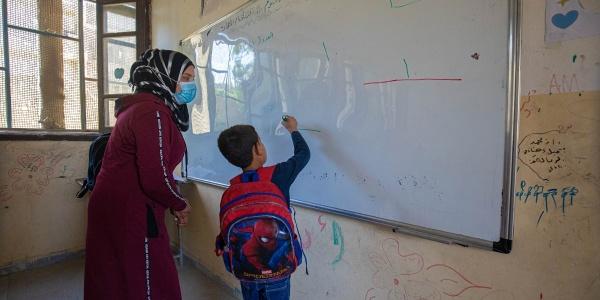 Un bambino con lo zaino in spalla scrive su una lavagna di spalle. Vicino a lui una donna con un vestito lungo e il chador, indossa anche la mascherina e guarda quello che scrive il bambino.