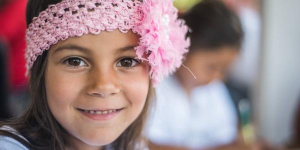 Primo piano bambina sorridente con fascia rosa in testa