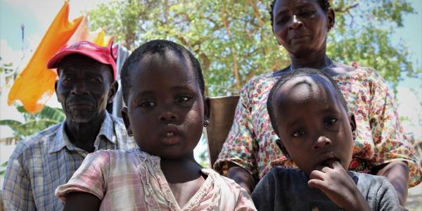 Due bambini del Mozambico in primo piano e dietro di loro un uomo e una donna guardano in camera ripresi leggermente dal basso. Uno dei bambini ha un dito in bocca e una maglietta nera, l altra ha un vestitino bianco