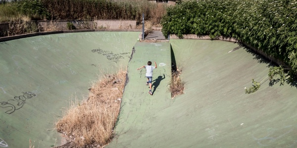 Un bambino di spalle corre in uno degli spazi abbandonati di Ponte di Nona a Roma