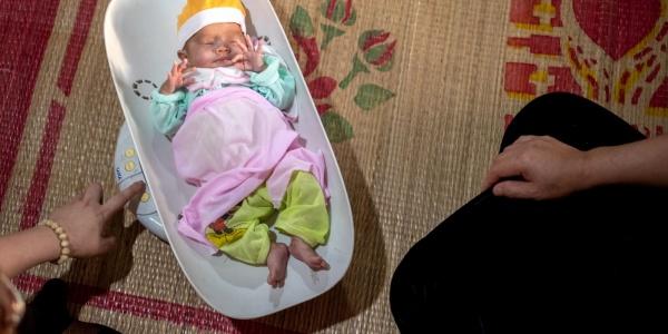 neonato in una vaschetta di plastica per pesarlo, vestito con vestitini caldi e colorati