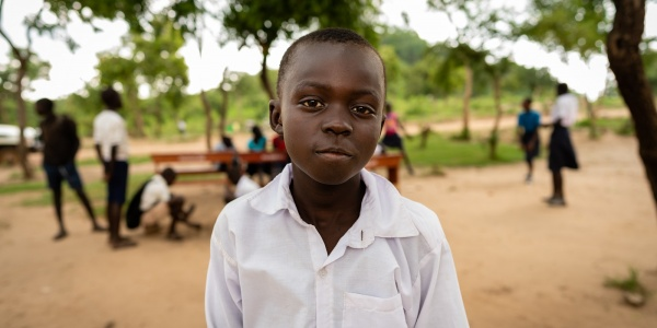 Bambino africano con divisa della scuola in un campo rifugiati