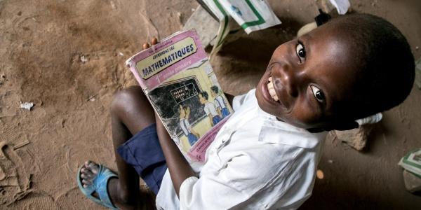 Bambino Repubblica Democratica del Congo foto dall'alto è seudto e guarda in camera tenendo dei libri di scuola in mano.