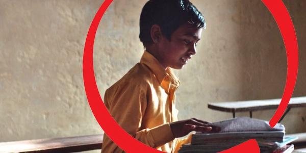 bambino al banco di scuola che scrive