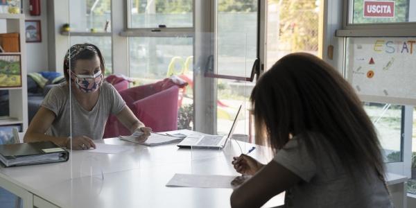 operatrice di Save the Children con mascherina e una donna di spalle sedute entrambe a un tavolo divise da un plexiglas per la protezione da covid-19