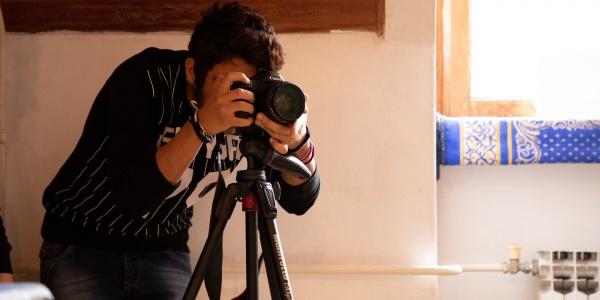 operatore video chinato sulla sua videocamera mentre fa delle riprese in una stanza