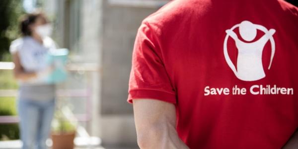 operatore save the children di spalle con maglietta brandizzata in primo piano. Sullo sfondo una figura di donna sfocata