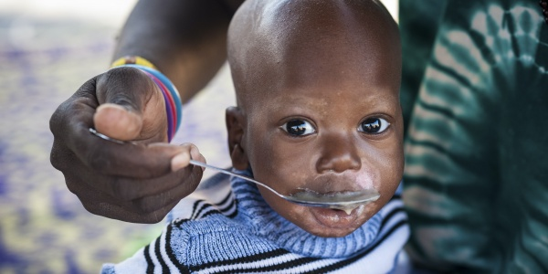 Primo piano di un bambino del Burkina Faso che viene imboccato con un cucchiao da una donna di cui si vede solo la mano e un pezzo di vestito verde