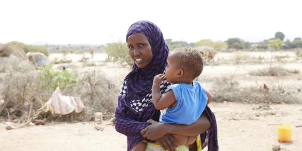 foto mezzo busto mamma con velo con il suo bambino in braccio, all aperto in una area colpita da siccità